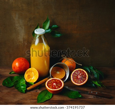 Still Life with Ripe Juicy Citrus Fruits on Wooden Table with Bottle of Fresh Squeezed Orange Juice. Vibrant Colors, Square Composition. - stock photo