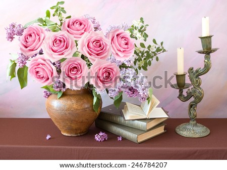 Still life with roses and lilac flowers, books and candlestick on artistic background - stock photo