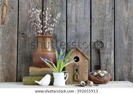 Still life with Russian clay jag, bird house, nest, quail eggs,bunch of willows, bouquet of fresh blue hyacinths, wooden eggs,very old rusty key, white  vintage  porcalain bird,antique books - stock photo