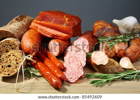 Still Life with salami, sausages, baguette and rosemary on a wooden table. - stock photo