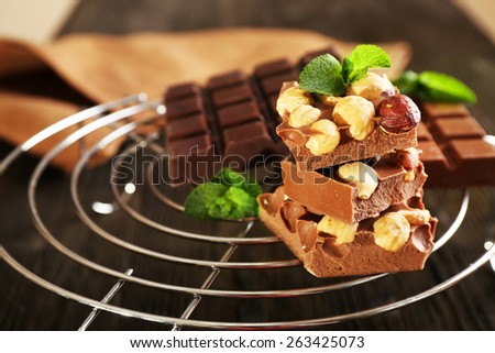 Still life with set of chocolate and nuts on metal stand, closeup - stock photo