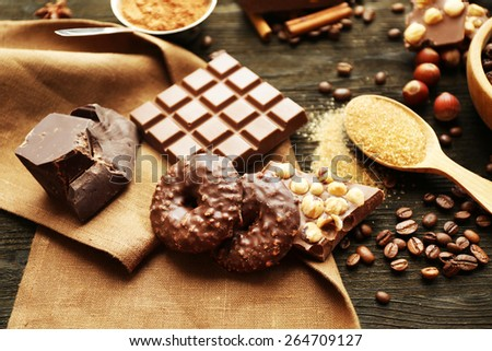 Still life with set of chocolate, nuts and spices on wooden table, closeup - stock photo