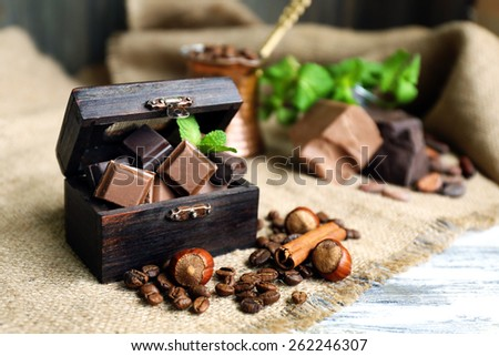 Still life with set of spicy chocolate, nuts and coffee beans on burlap cloth, closeup - stock photo