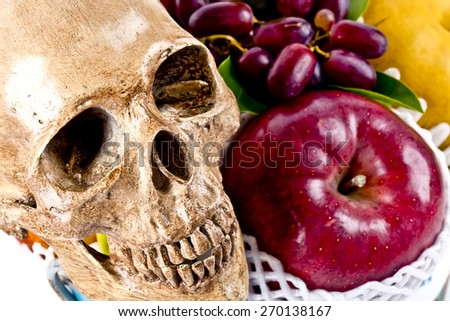 still life with skull and fruits on background - stock photo