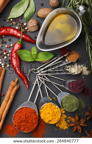 still life with spices and olive oil over dark slate background - stock photo