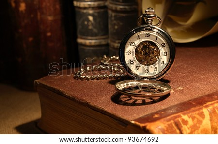 Still life with stylish pocket watch on ancient book - stock photo