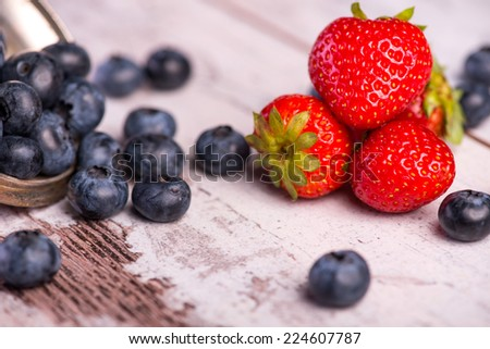 Still life with the copper top and little blackberries in it scattering on the wooden table amid the tempting red strawberries - stock photo