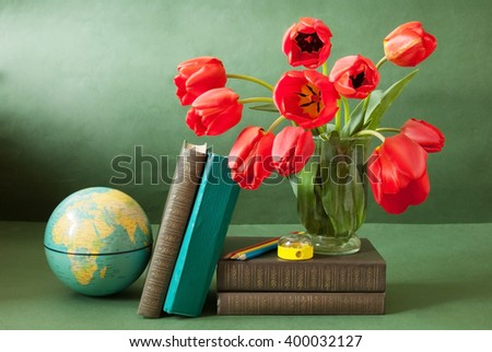 Still life with tulips bunch, book pile, globe and pencil on artistic background. World Teacher's Day concept - stock photo