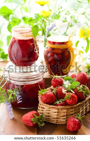 Still life with various types of strawberry jam and fresh strawberries - stock photo