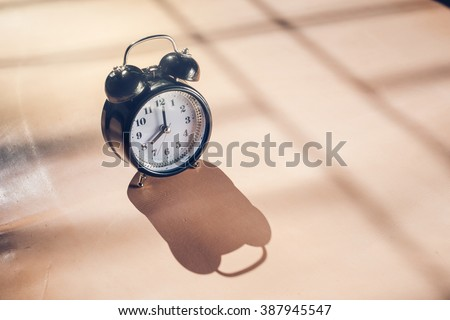 Still life with vintage alarm clock on leather.( alarm clock show 8 o`clock ) - stock photo