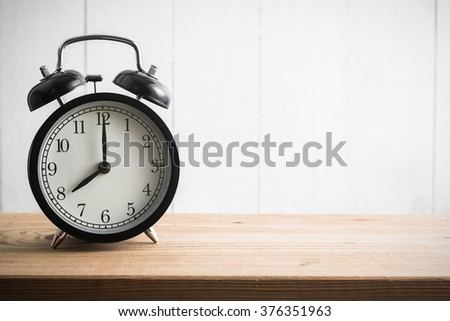 Still life with vintage alarm clock on wood table ( alarm clock show 8 o`clock ) - stock photo