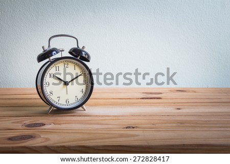 Still life with vintage clock on wooden table over grunge background - stock photo