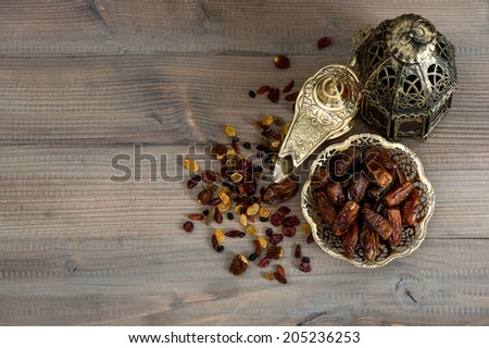 Still life with vintage oriental lantern, raisins and dates on wooden background - stock photo