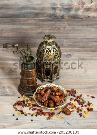 Still life with vintage orintal latern and mill. Raisins and dates on wooden background - stock photo