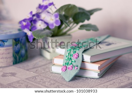 Still life with violets, books and a bookmark - stock photo