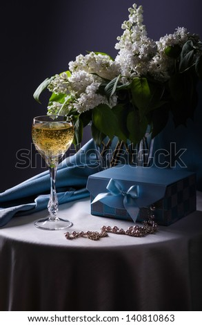 Still life with white lilac in glass vase - stock photo