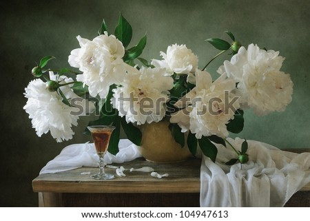 Still life with white peonies and a glass of wine - stock photo