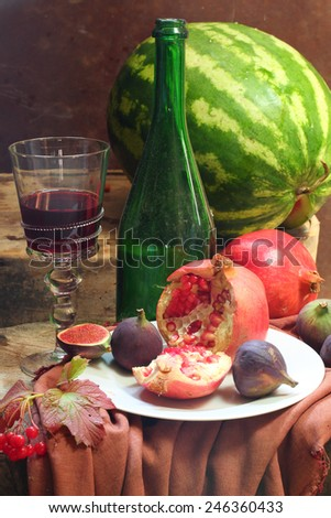 Still-life with wine, a pomegranate, a fig and a water-melon  - stock photo