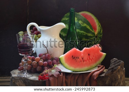 Still-life with wine, a water-melon, grapes, a guelder-rose and a white jug - stock photo