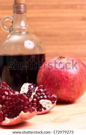 Still-life with wine and garnet on the wood table - stock photo
