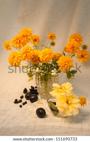 still life with yellow flowers and berries - stock photo