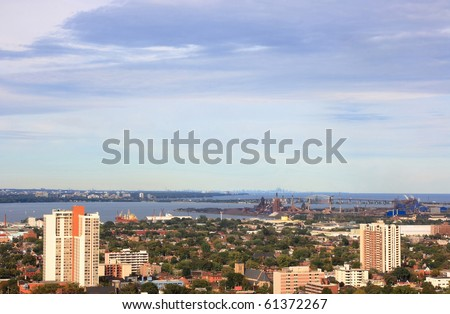 Still Picture of part of Hamilton, Ontario, Canada with industrial area and the Lake Ontario with silhouette of Toronto and CN Tower on background. - stock photo