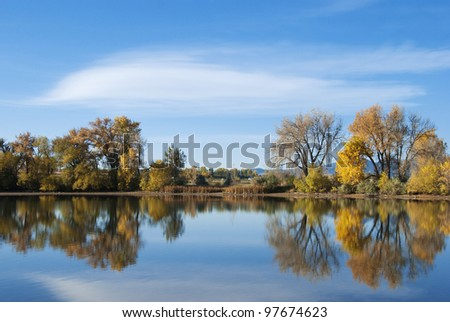 Still pond or lake on the Colorado prairie in early autumn with golden autumn colors - stock photo