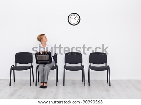 Still waiting for the job interview - woman checking time - stock photo