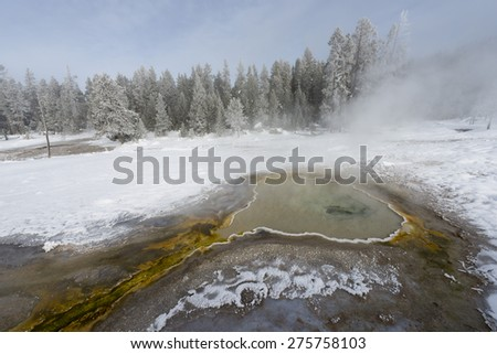 Still waters of a geyser in snow-covered landscape. Yellowstone National Park. - stock photo