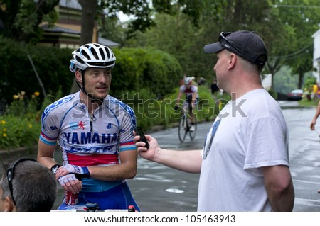 STILLWATER, MINNESOTA - JUNE 17: Reporter interviews pro cyclist Christian Helmig following victory at final stage of Nature Valley Grand Prix at Criterium on June 17, 2012 in Stillwater - stock photo