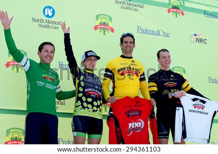 STILLWATER, MN/USA - JUNE 21, 2015: Winners of Amateur Omnium race categories wave to crowd from podium during celebration event at finish of prestigious North Star Grand Prix in Stillwater. - stock photo