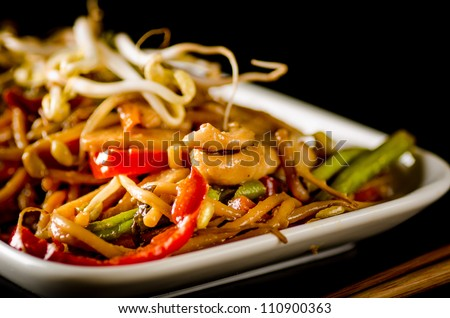 Stir-fried chinese noodles with chicken, vegetables and beansprouts on black - stock photo