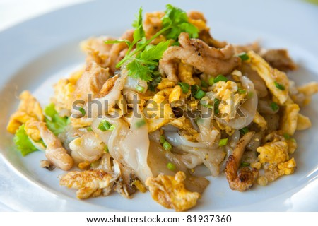 Stir fried noodles with egg, pork, green vetgetables, and sweet soy bean sauce - stock photo