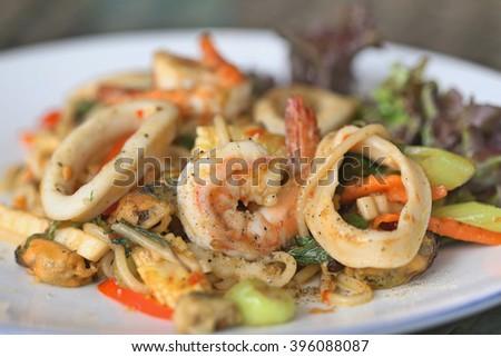 stir-fried spicy spaghetti with seafood. thai style stir-fried spicy spaghetti with seafood. stir-fried spicy pasta with seafood. - stock photo