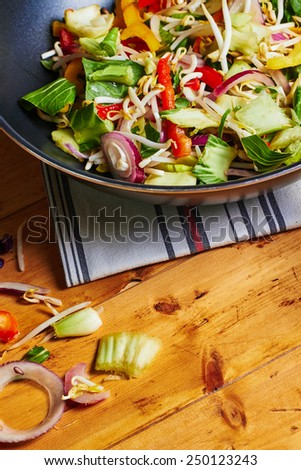 Stir fry vegetables in a wok, wooden table and ingredients  - stock photo