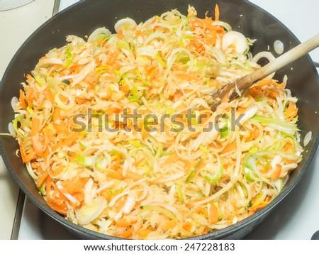 Stir frying shredded vegetables in large pan - stock photo