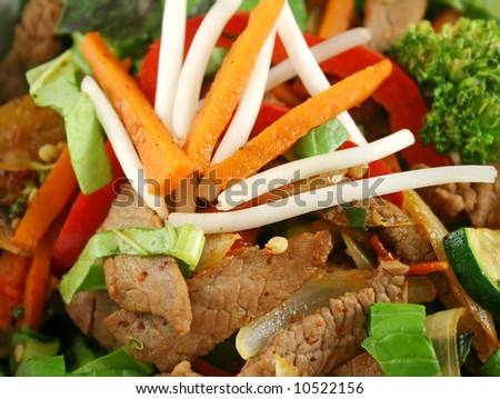 Stirfry beef and vegtables with a purple green basil garnish. - stock photo