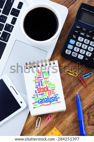 Stock Analysis word cloud arrangement concept on note nook. Notebook,smartphone, calculator and a cup of coffee on wooden table. - stock photo