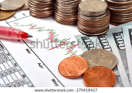 stock candle chart and dollar money on table - stock photo