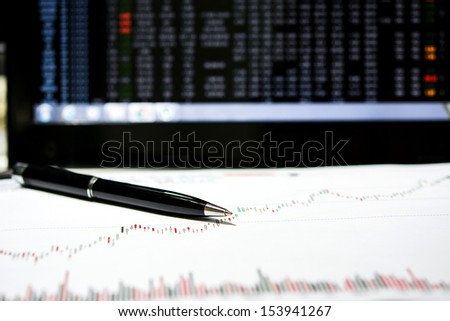 stock chart paper and pen with laptop monitor - stock photo