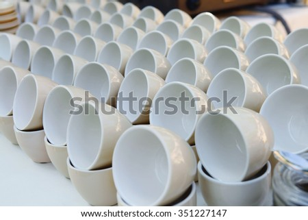 stock coffee cups served on white table as at coffee shop - stock photo