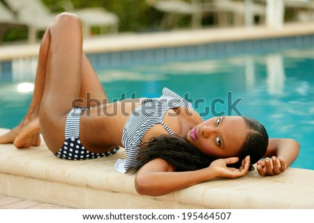 Stock image of a laying by the pool with arms above head - stock photo