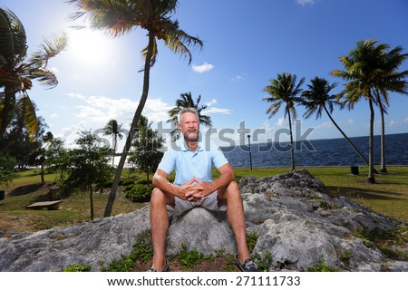 Stock image of a old man sitting on a rock - stock photo