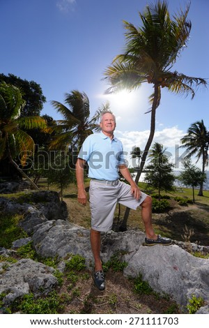 Stock image of a senior old man posing in a nature setting with his leg on a rock - stock photo