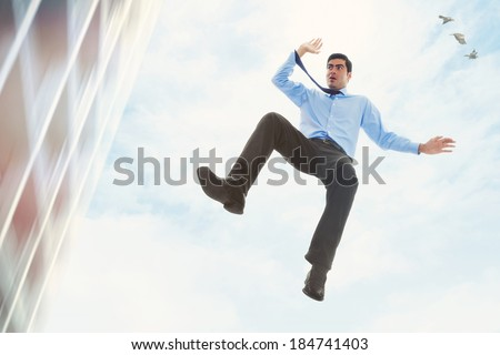 Stock image of businessman falling off a building - stock photo