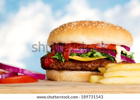 Stock image of cheeseburger with fries outdoors on wooden plate - stock photo