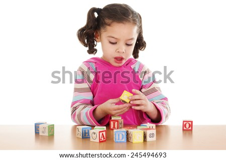 Stock image of child playing with cube letters over white background - stock photo