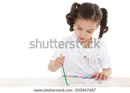 Stock image of female preschooler playing with watercolors over white background - stock photo
