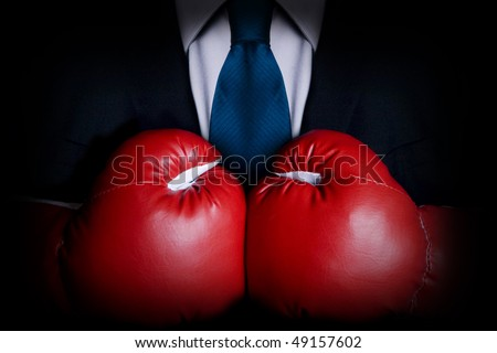 Stock image of person wearing business suit and boxing gloves - stock photo