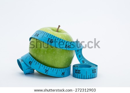 stock image of the green apple and measuring tape - stock photo